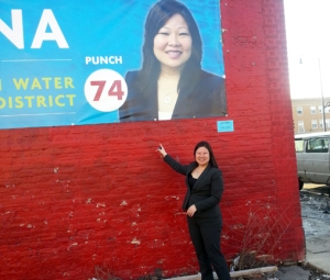 Morita standing in front of campaign banner at the Proviso Democrats Office.